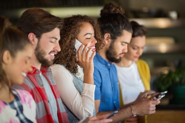Юные друзья с помощью мобильных телефонов Premium Фотографии