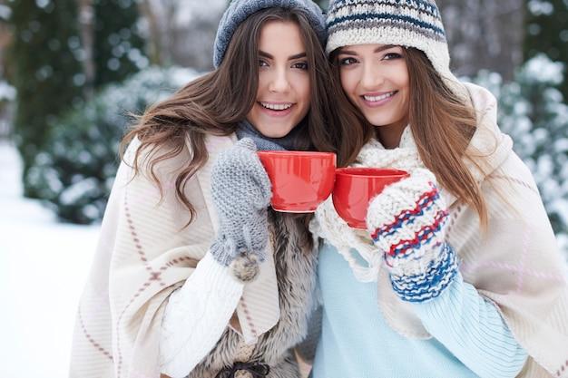 冬に温かい飲み物を持つ若い友人 無料写真