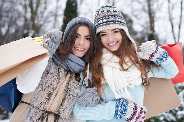 冬の買い物袋を持つ若い友人 無料写真