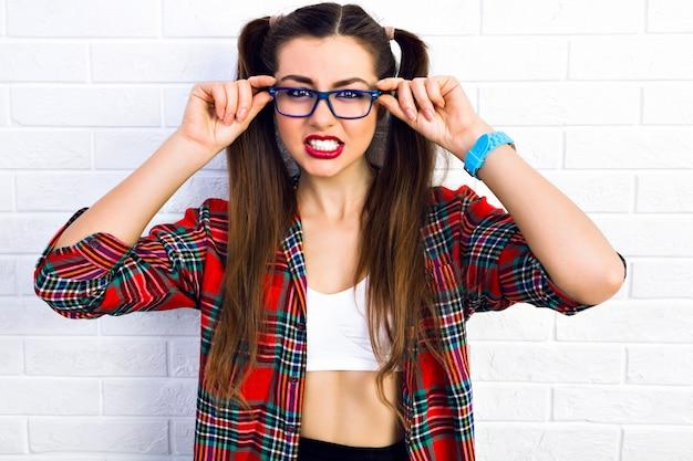 若いおかしい生意気な女性、変な怒った顔をして、彼女の歯を見せて、明るいメイク、長いビュートヘア、流行に敏感なメガネ、格子縞のシャツ、一人で夢中になる。 無料写真