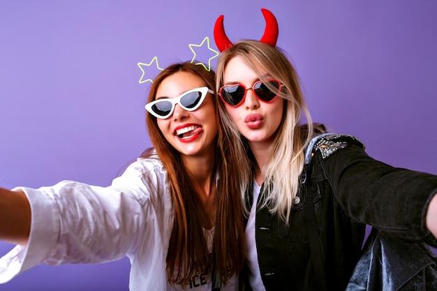 Молодые веселые девушки делают селфи, винтажные очки, повязки для волос на вечеринку дьявола и звезд, повседневную молодежную одежду, позитивное настроение. Бесплатные Фотографии