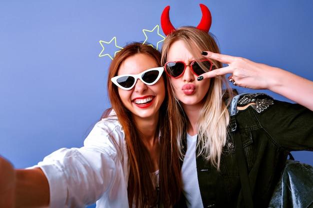 自分撮り、ヴィンテージのメガネ、悪魔と星のパーティーヘアバンド、カジュアルな若者服、前向きな気分を作る面白い女の子。 無料写真