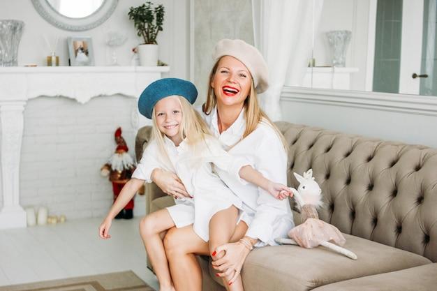 若い面白い幸せな公正な長い髪のお母さんとかわいい女の子のリビングルーム、幸せな家族のライフスタイルで一緒に楽しんで Premium写真