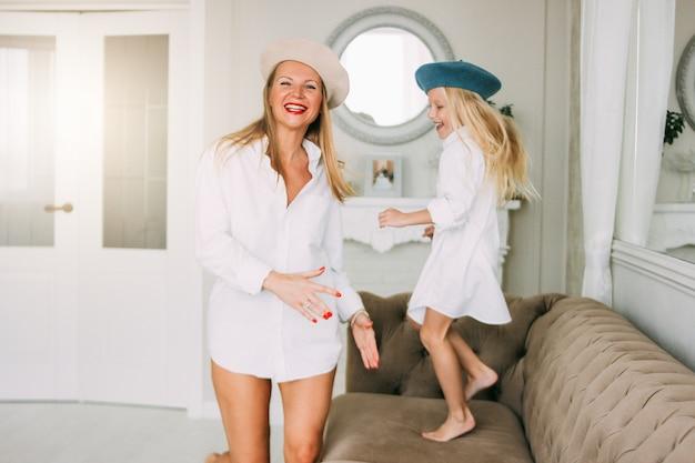 若い面白い幸せな公正な長い髪のお母さんと彼女のかわいい女の子のリビングルーム、幸せな家族のライフスタイルで一緒に踊って楽しんで Premium写真