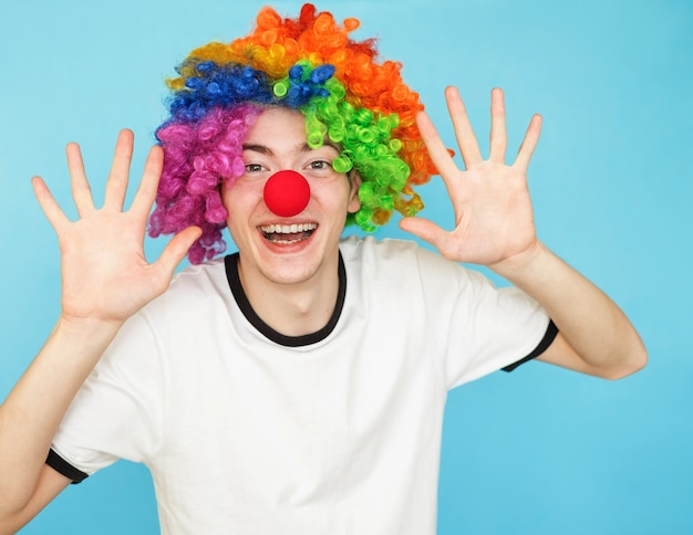 Young funny male teenager in white t-shirt in clown wig Premium Photo
