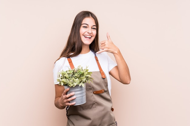 Young gardener caucasian woman holding a plant isolatedshowing a mobile phone call gesture with fingers. Premium Photo