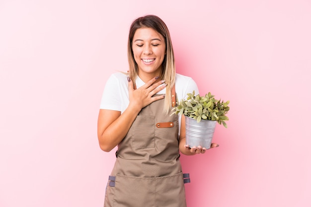 Young gardener caucasian woman laughs out loudly keeping hand on chest. Premium Photo