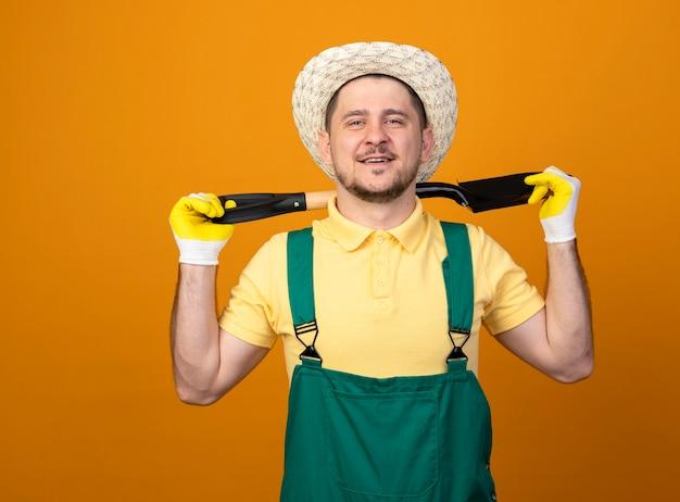 Giovane giardiniere in tuta e cappello tenendo la pala sulla sua spalla guardando davanti sorridente fiducioso in piedi sopra la parete arancione Foto Gratuite
