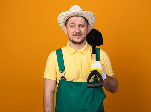 Giovane giardiniere in tuta e cappello tenendo la pala guardando davanti sorridente fiducioso in piedi sopra la parete arancione Foto Gratuite