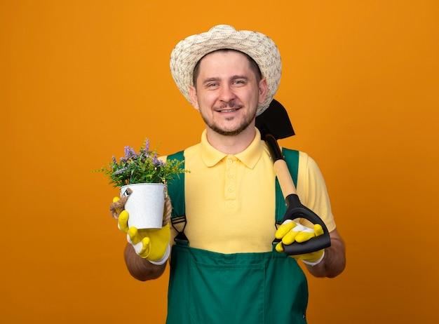 Giovane giardiniere in tuta e cappello tenendo la pala e la pianta in vaso guardando la parte anteriore sorridente con la faccia felice in piedi sopra la parete arancione Foto Gratuite