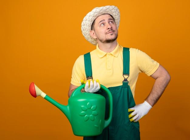 Giovane giardiniere in tuta e cappello tenendo annaffiatoio alzando lo sguardo perplesso sopra la parete arancione Foto Gratuite