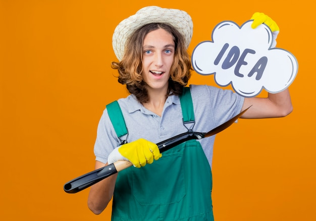 Young gardener man in rubber gloves wearing jumpsuit holding shovel and speech bubble Free Photo