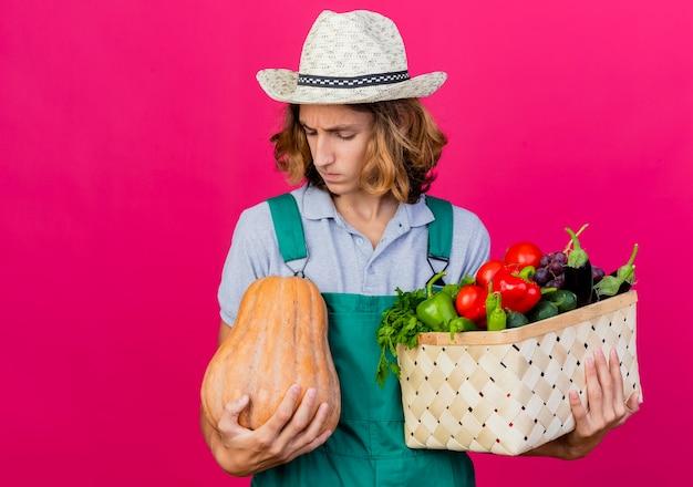 新鮮な野菜でいっぱいの木枠を保持しているジャンプスーツと帽子を身に着けている若い庭師の男 無料写真