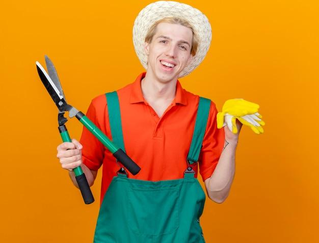 オレンジ色の背景の上に立っている幸せそうな顔で元気に笑ってカメラを見てヘッジクリッパーとゴム手袋を保持しているジャンプスーツと帽子を身に着けている若い庭師の男 無料写真