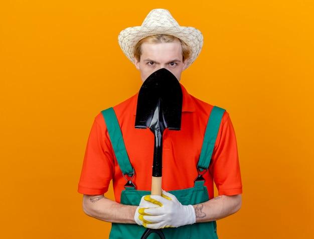 オレンジ色の背景の上に立っている彼の顔を隠しているカメラを見てシャベルを保持しているジャンプスーツと帽子を身に着けている若い庭師の男 無料写真