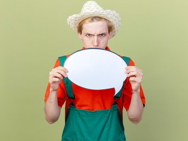 Young gardener man wearing jumpsuit and hat showing blank speech bubble sign looki at camera with serious face frowning standing over light background Free Photo