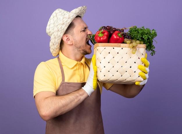 보라색 벽 위에 서있는 야채를 물려고하는 야채 가득한 상자를 들고 작업 장갑에 죄수 복과 모자를 쓰고있는 젊은 정원사 무료 사진
