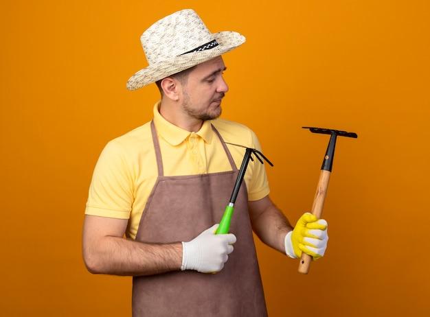 Giovane giardiniere che indossa tuta e cappello azienda mattock e mini rastrello guardandoli con faccia seria in piedi sopra la parete arancione Foto Gratuite