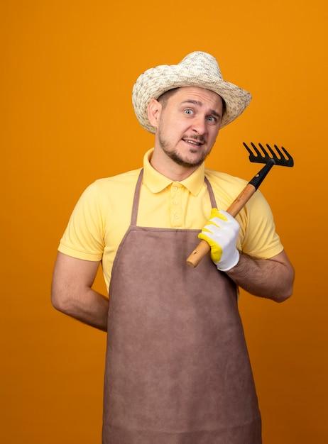 Giovane giardiniere che indossa tuta e cappello tenendo mini rastrello guardando davanti sorridente confuso in piedi sopra la parete arancione Foto Gratuite