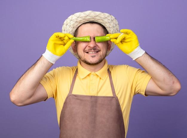 Giovane giardiniere che indossa tuta e cappello in guanti da lavoro in possesso di peperoncino verde rotto sopra gli occhi sorridenti in piedi sopra la parete viola Foto Gratuite