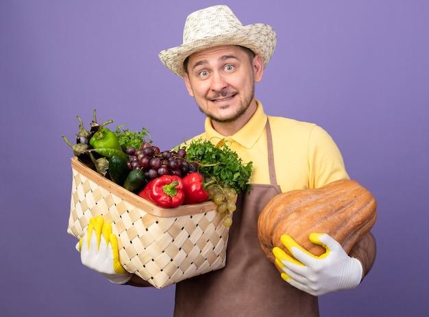 Giovane giardiniere che indossa tuta e cappello in guanti da lavoro tenendo la cassa piena di verdure con zucca guardando davanti sorridente con la faccia felice in piedi sopra la parete viola Foto Gratuite