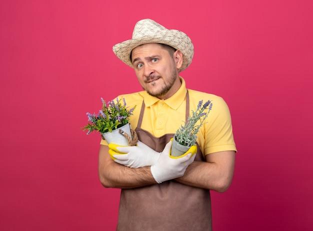 Giovane giardiniere che indossa tuta e cappello in guanti da lavoro in possesso di piante in vaso guardando davanti confuso in piedi sopra il muro rosa Foto Gratuite
