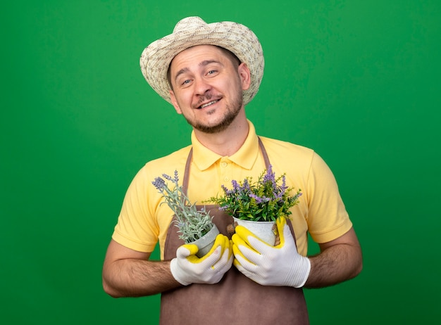 Giovane giardiniere che indossa tuta e cappello in guanti da lavoro tenendo piante in vaso guardando la parte anteriore sorridente allegramente in piedi sopra la parete verde Foto Gratuite