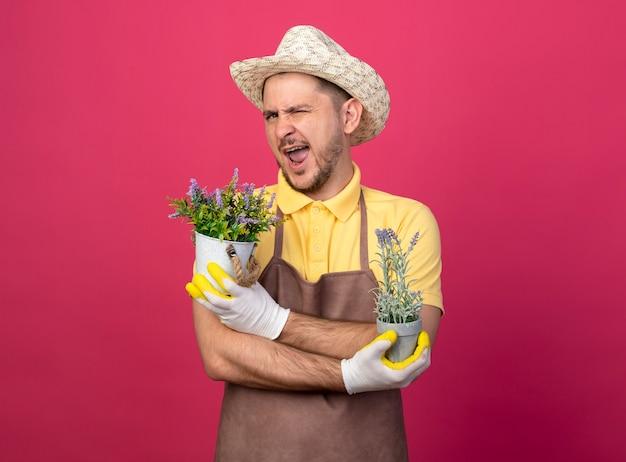 Giovane giardiniere che indossa tuta e cappello in guanti da lavoro che tengono piante in vaso guardando davanti sorridente e ammiccante in piedi sopra il muro rosa Foto Gratuite