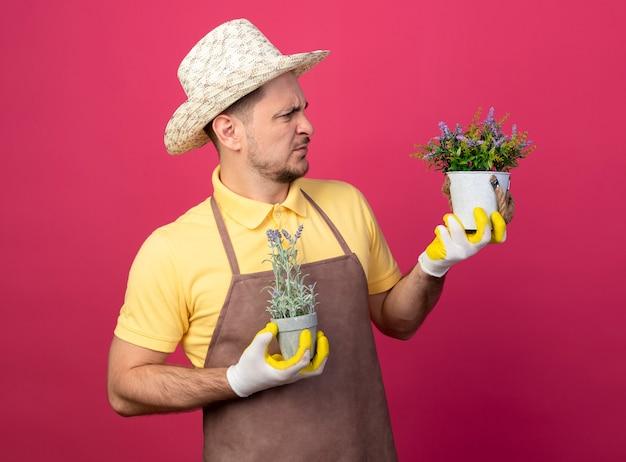 Giovane giardiniere che indossa tuta e cappello in guanti da lavoro tenendo le piante in vaso guardandole confuso e scontento in piedi sopra il muro rosa Foto Gratuite