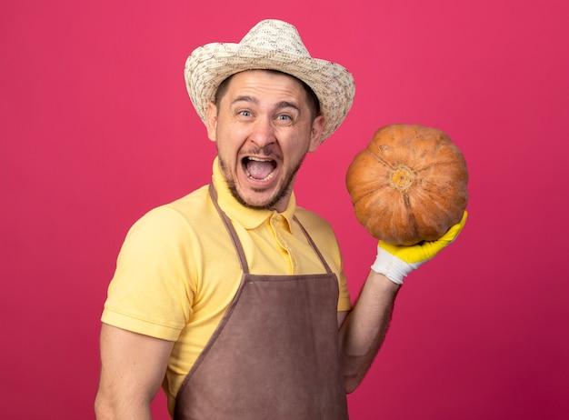 Giovane giardiniere che indossa tuta e cappello in guanti da lavoro tenendo la zucca guardando davanti sorridente con la faccia felice eccitato in piedi sopra la parete rosa Foto Gratuite