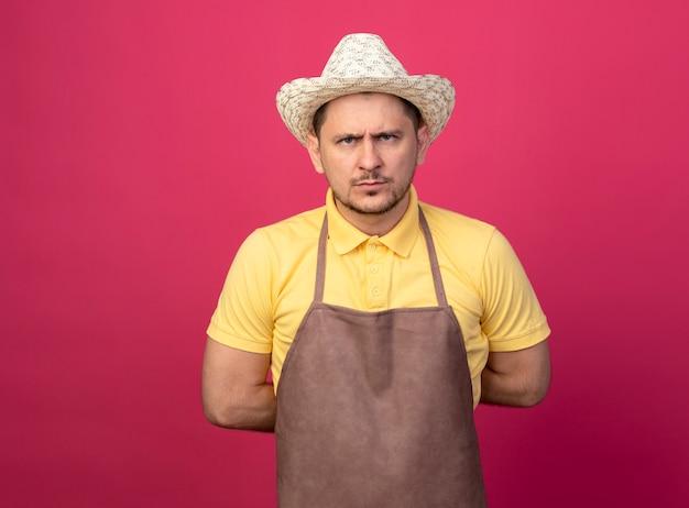 Giovane giardiniere che indossa tuta e cappello in guanti da lavoro guardando davanti con faccia seria dispiaciuta in piedi sopra il muro rosa Foto Gratuite