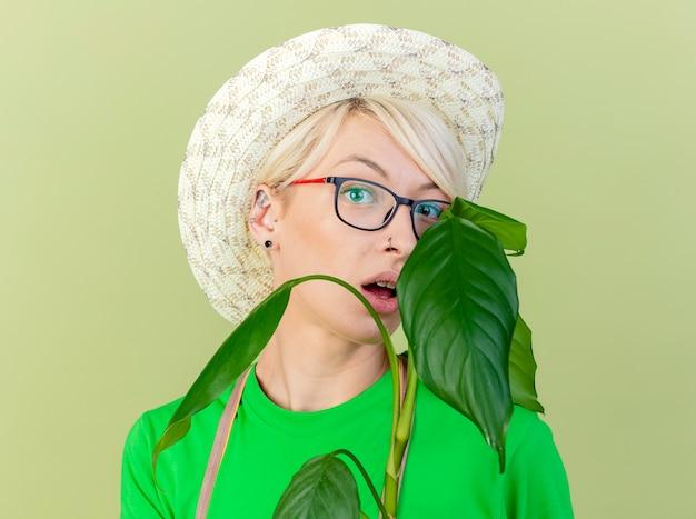 앞치마와 모자에 짧은 머리를 가진 젊은 정원사 여자는 밝은 배경 위에 서 놀란 카메라를보고 공장을 들고 무료 사진
