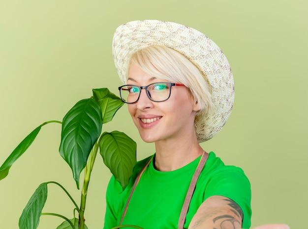 明るい背景の上に立っている顔に笑顔でカメラを見てエプロンと帽子保持植物の短い髪の若い庭師の女性 無料写真