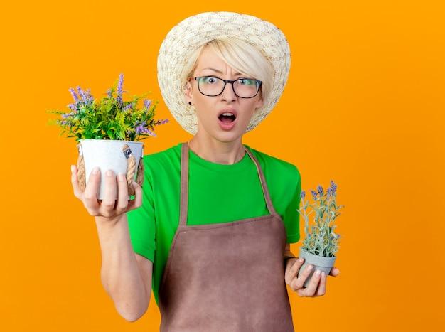 エプロンと帽子の短い髪の若い庭師の女性は、オレンジ色の背景の上に立って驚いて驚いているカメラを見て鉢植えの植物を保持しています 無料写真