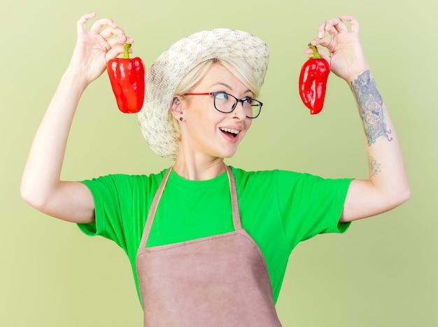 エプロンと帽子の短い髪の若い庭師の女性は、明るい背景の上に元気に立って笑顔を楽しんで赤ピーマンを保持しています 無料写真