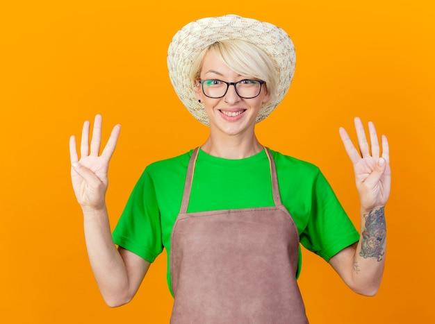 エプロンと帽子の短い髪の若い庭師の女性がオレンジ色の背景の上に立って笑顔で8番を指で上向きに表示します 無料写真