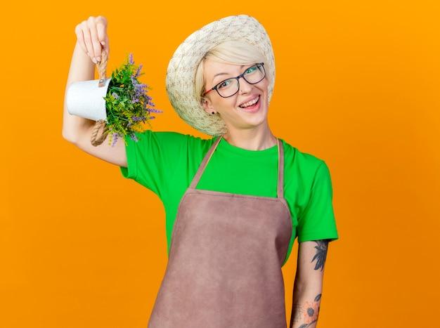 エプロンと帽子の短い髪の若い庭師の女性は、オレンジ色の背景の上に立って幸せそうな顔で笑顔のカメラを見て鉢植えの植物を示しています 無料写真