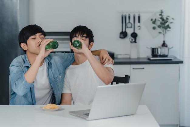 若い同性愛者のカップルは、現代の家でコンピューターのラップトップを使用しながらビールを飲みます。アジアのlgbtq男性は、家の台所でテーブルに座ってソーシャルメディアを一緒に再生する技術を使用して楽しいリラックスを楽しんでいます。 無料写真