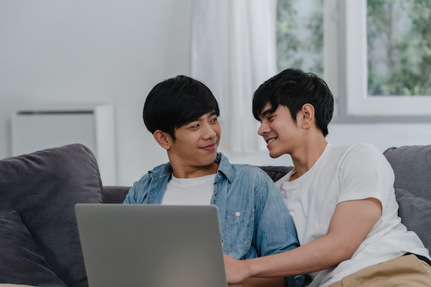 Young gay couple using computer laptop at modern home. asian lgbtq+ men happy relax fun using technology watching movie in internet together while lying sofa in living room at house . Free Photo