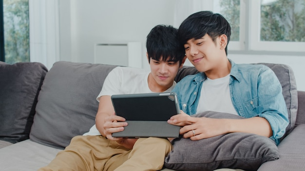 Young gay couple using tablet at home. asian lgbtq+ men happy relax fun using technology watching movie in internet together while lying sofa in living room . Free Photo