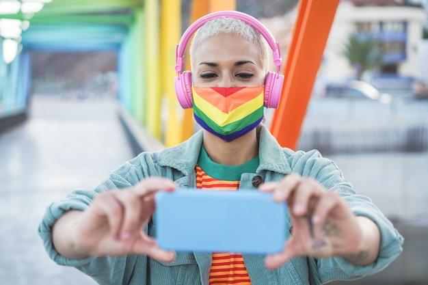 携帯電話で屋外で自分撮りをしている若いゲイの女性-虹色の旗を身に着けている技術トレンドを楽しんでいる女の子-lgbtの概念 Premium写真