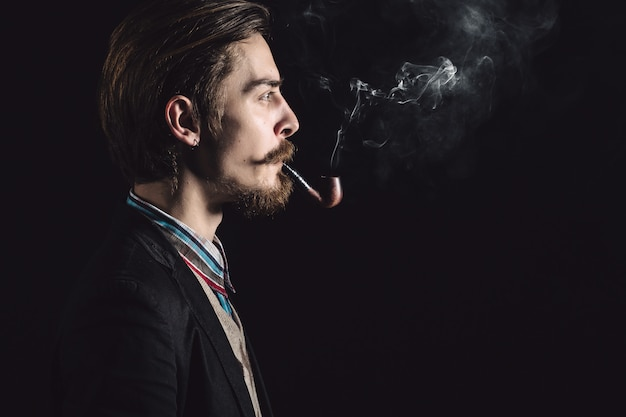 Young gentlemen smokes a pipe Free Photo