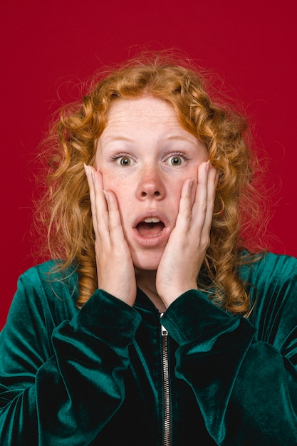 Young ginger shocked woman holding cheeks Free Photo