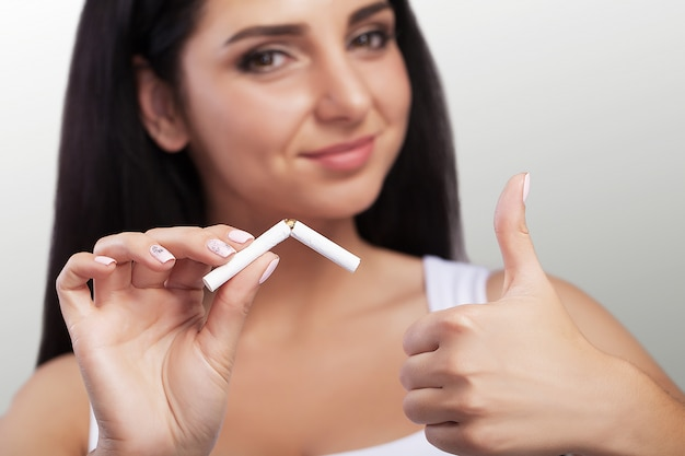 Young girl against smoking. macro photography. broken cigarette in the hands of a young girl who is against smoking. Premium Photo