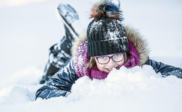若い女の子が雪で遊んでいる凍るような冬の公園で幸せな女の子にクローズアップ Premium写真