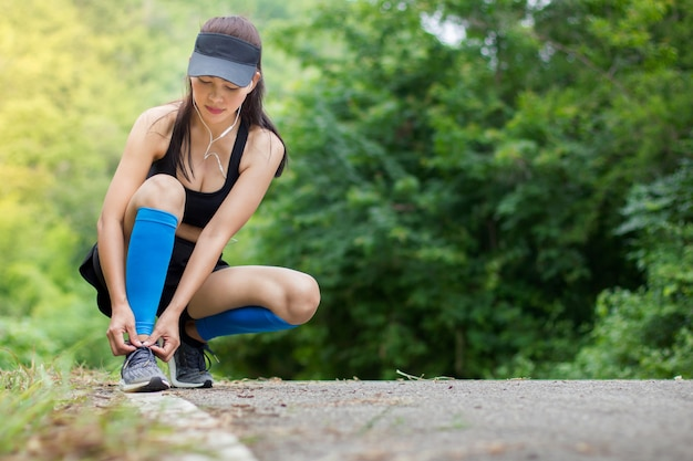 Young girl asian wear earphone knelt down to do up his shoelaces after running exercise Premium Photo