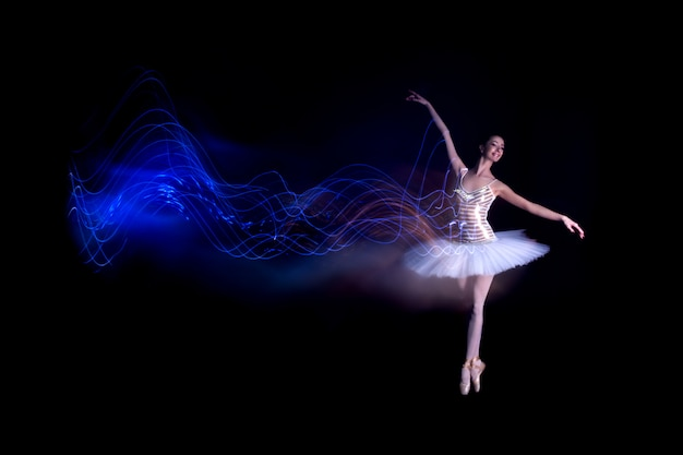Young girl ballerina with tutu solo dancing doing stand on toes and leaves blue light leak trail of silhouette in black scene with reflecting floor Premium Photo
