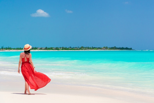 Young girl in beautiful red dress in the beach Premium Photo