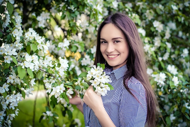 Young girl beside a blossoming apple tree Premium Photo