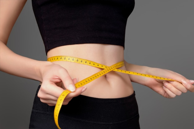 A young girl in black sportswear measures her waist with a centimeter on a dark gray background, slim waist. healthy athletic body, diet, weight loss, calorie count. slimming concept Premium Photo